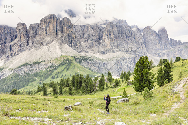 Unrecognizable kid taking photo of Dolomites mountain ridge while standing in Val Badia valley on cloudy day in Italy