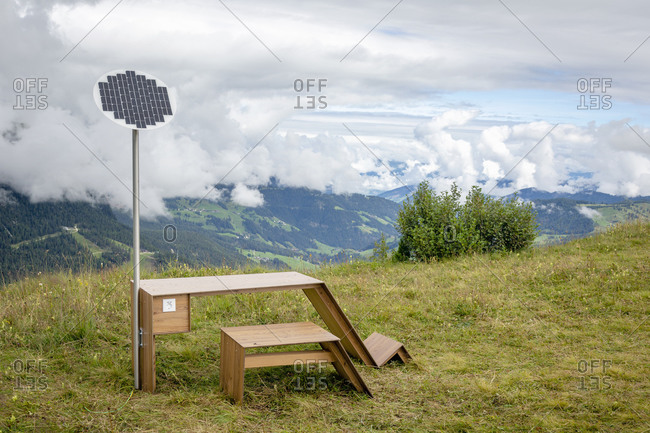 Modern table with solar panel and electric socket located near bench in Dolomites mountains on cloudy day in Italy