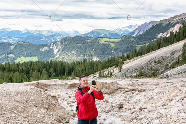 Middle aged man in outerwear smiling and taking photo of Dolomites mountain ridge during trip in Italy