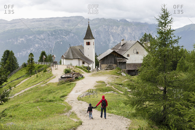 Back view of anonymous man and kid in outerwear holding hands and walking along path towards old church during trip in Dolomites mountains in Italy
