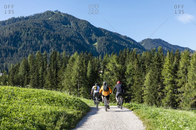 Back view of anonymous travelers in helmets riding bicycles on countryside road in green Val Badia valley towards coniferous forest on sunny summer day in Dolomites mountains in Italy