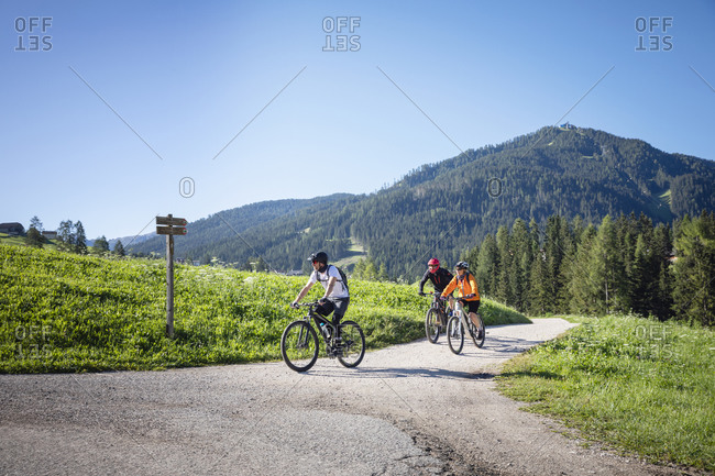 Group of friends in helmets riding bicycles on countryside road near forest in Val Badia valley against Dolomites mountains on cloudless day in Italy