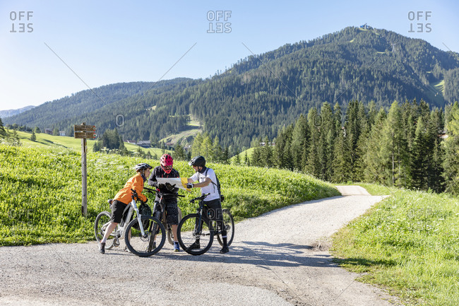 Full body men and woman on bicycles examining map and navigating through Dolomites mountains while standing on road in Val Badia valley in summer in Italy