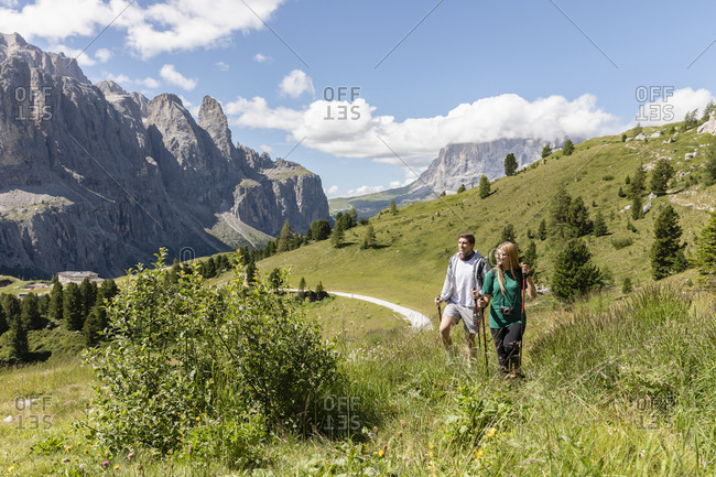 Young man and woman with walking sticks looking away while exploring grassy Val Badia valley near Dolomites mountains on summer day in Italy