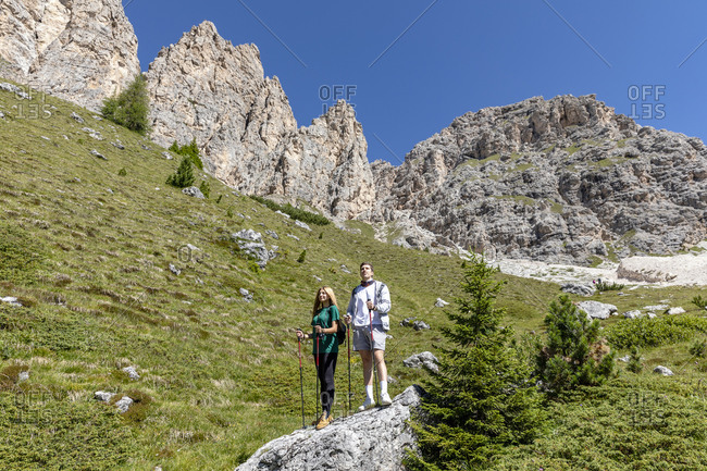 Full body male and female hikers with walking sticks standing on stone near Dolomites mountains and admiring Val Badia valley on sunny summer day in Italy