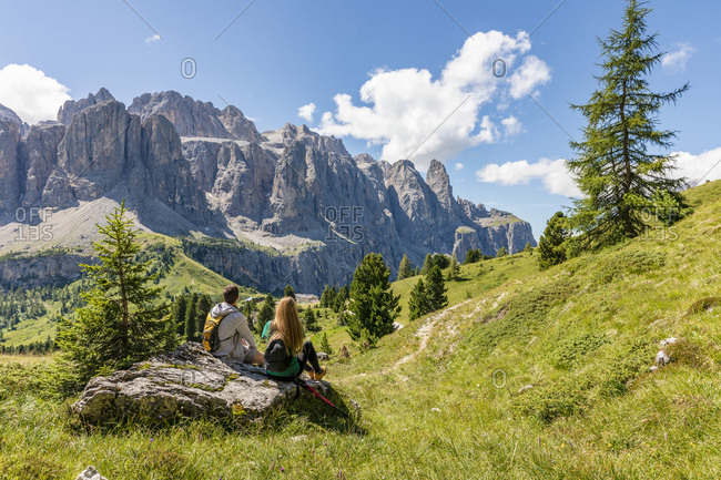 Back view of unrecognizable man and woman with backpacks sitting on rock in Val Badia valley and admiring Dolomites mountain ridge on sunny day in Italy