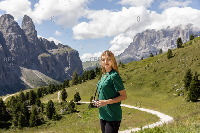 Young woman with photo camera looking at camera while standing near curvy path in green Val Badia valley against Dolomites mountains and cloudy sky in summer in Italy