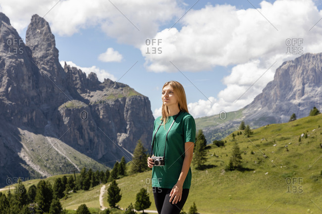 Young female traveler with photo camera looking away while standing in amazing Val Badia valley in Dolomites mountains against cloudy sky on summer day in Italy