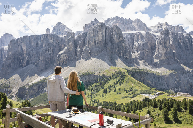 Back view of unrecognizable man and woman standing on wooden terrace and admiring Dolomites mountain ridge and Val Badia valley in summer in Italy