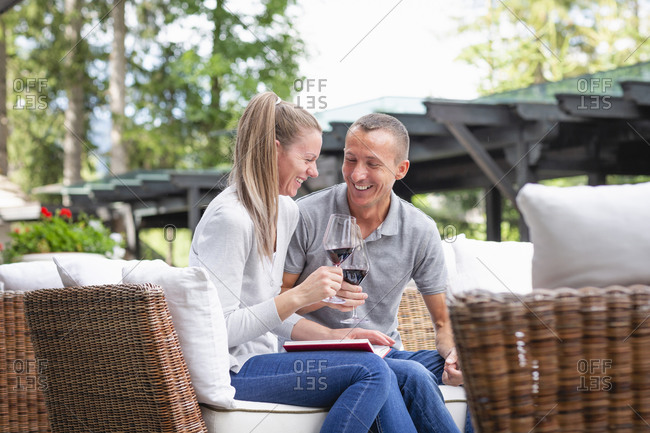 Adult man and woman smiling and clinking glasses of wine while relaxing on wicker couch on terrace on summer day in Dolomites mountains in Italy