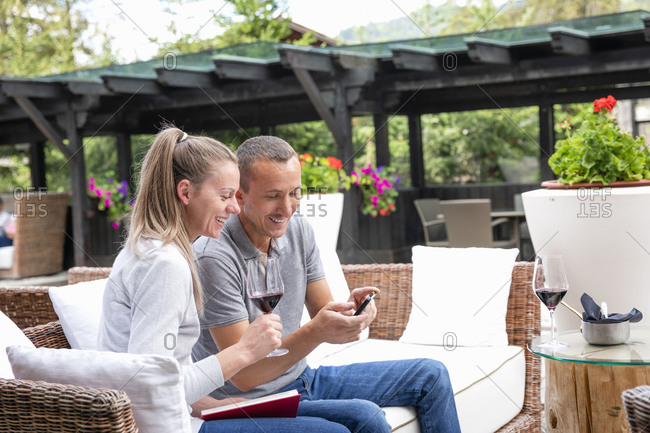 Happy adult man smiling and showing data on smartphone to cheerful woman with wine while resting on wicker sofa on terrace of restaurant in Dolomites in Italy