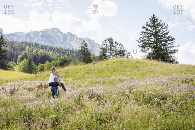 Back view of unrecognizable male carrying girlfriend on back while walking in blooming Val Badia valley near Dolomites mountains in summer in Italy