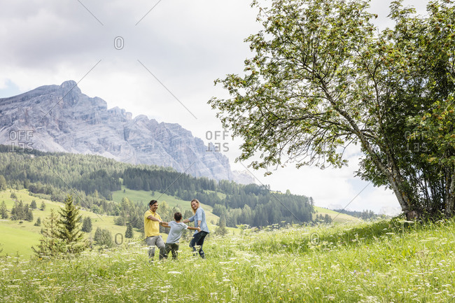 Cheerful parents and son holding hands and spinning around while having fun in grassy Val Badia valley near Dolomites mountains in summer in Italy