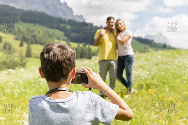 Back view of unrecognizable boy taking photo of mother and father in green Val Badia valley on sunny summer day in Dolomites mountains in Italy