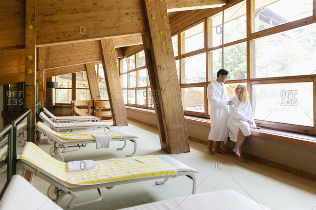 Positive man and woman in bathrobes looking at each other while relaxing near window in room with loungers on spa resort
