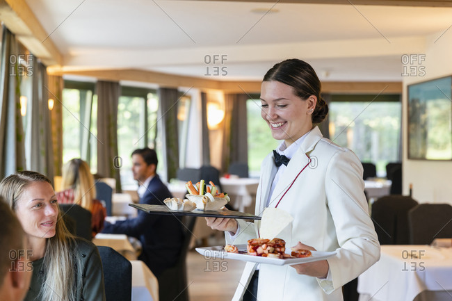 Positive woman in uniform smiling and carrying plates with exquisite food for clients while working in cozy restaurant