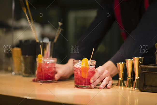 Unrecognizable barman putting glass cups with cold alcohol cocktails on counter while working in restaurant bar