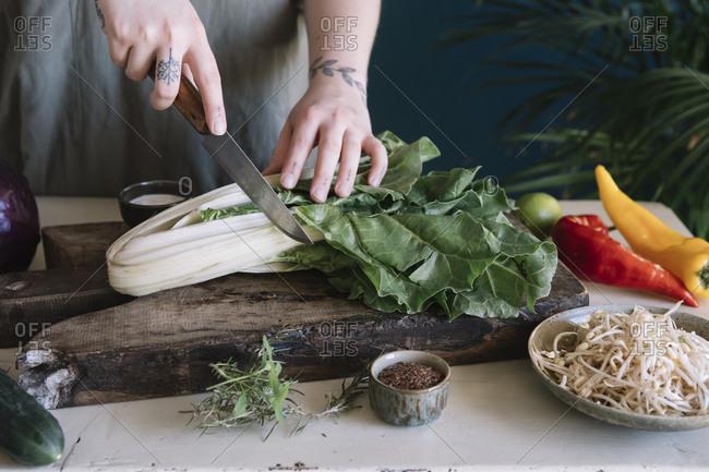 Young woman cutting pak choi on chopping board