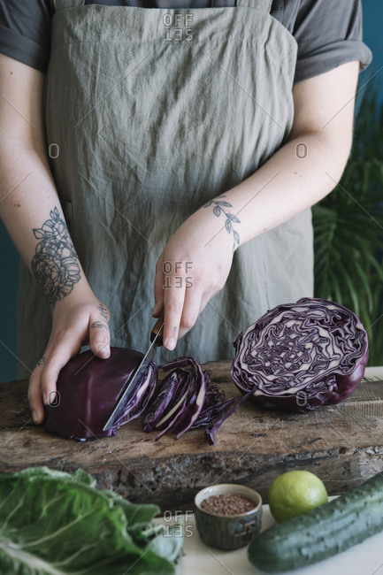 Young woman cutting red cabbage on cutting board