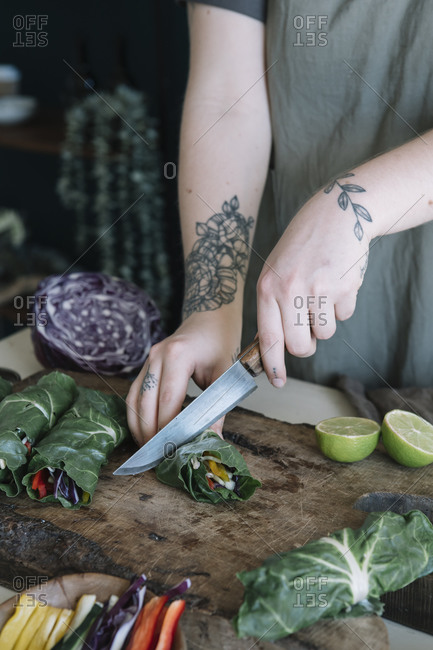 Young woman cutting vegan roll with vegetables on cutting board