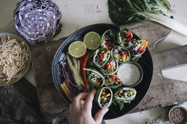 Woman's hand taking vegan roll with vegetables from bowl