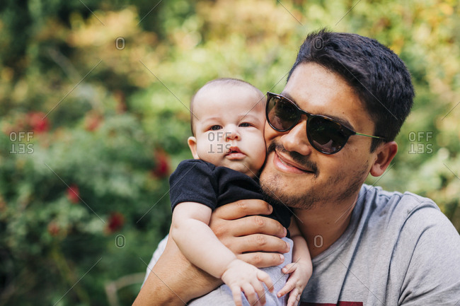 Loving man carrying cute son at park during weekend