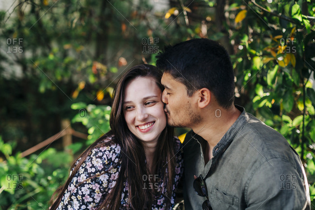 Young man with eyes closed kissing smiling woman at park