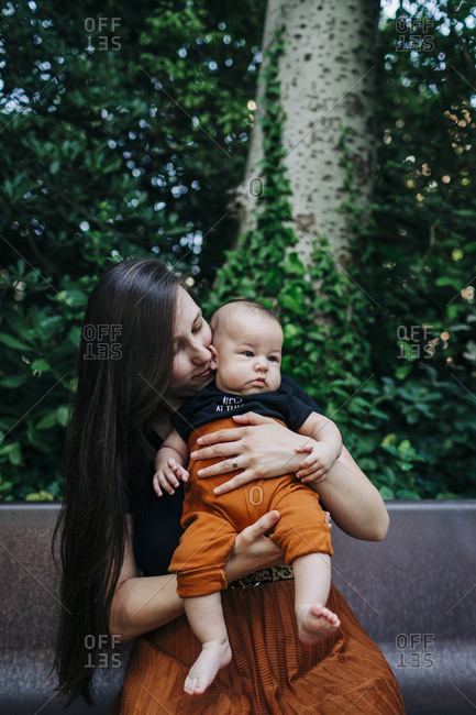 Young woman carrying baby boy while sitting on bench at park