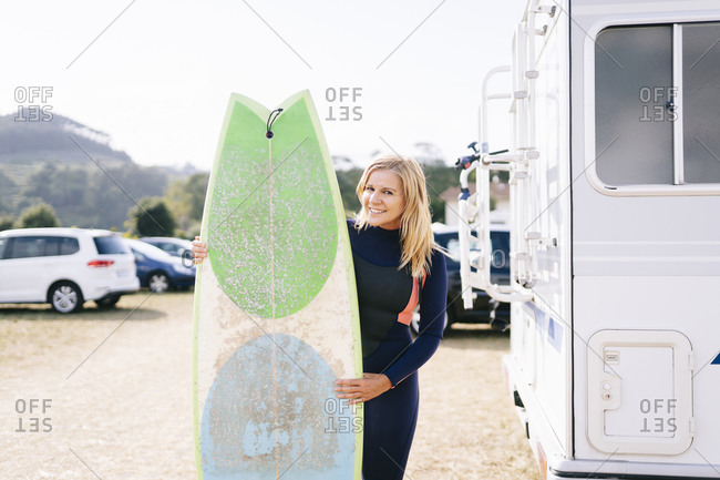 Beautiful woman smiling while holding surfboard by motor home during sunny day