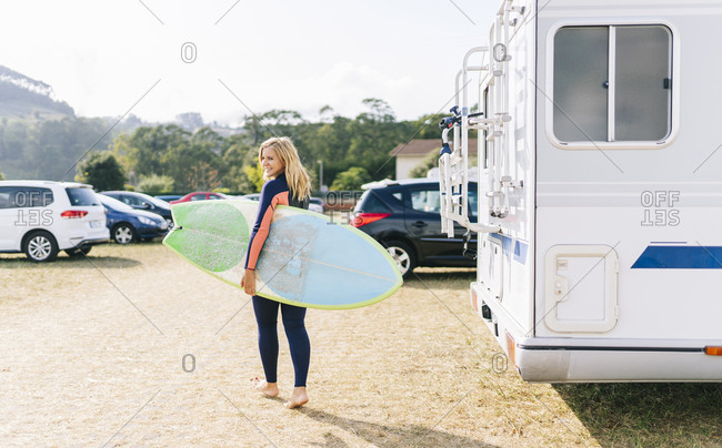 Woman walking with surfboard by motor home during sunny day