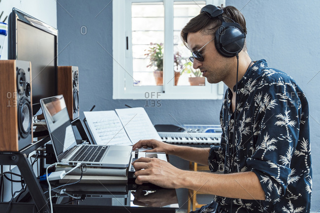 Man with headphones using laptop and keyboard at home