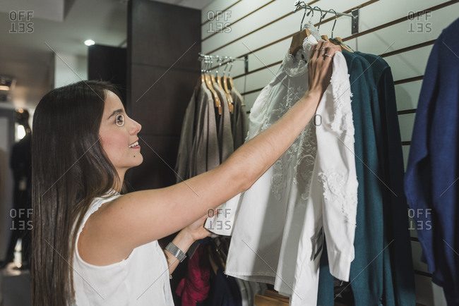 Happy young female customer choosing outfit for herself at store