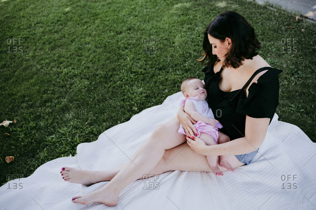Woman looking at cute baby girl sleeping on her laps while she is sitting in back yard