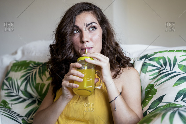 Beautiful young woman with long brown hair sipping juice from straw in mason jar while looking away