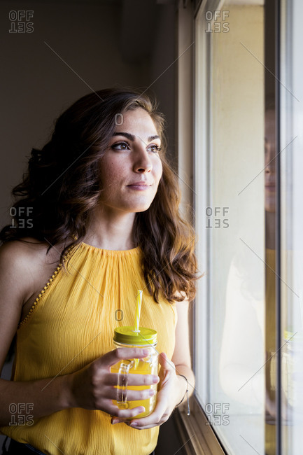 Thoughtful woman holding mason jar with juice while looking away through window at home