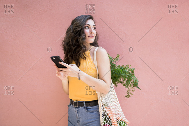 Young woman looking back while holding smart phone and standing with reusable mesh bag against pink wall