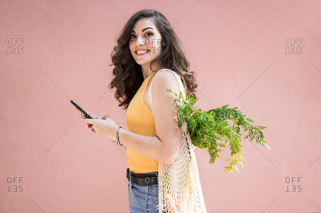 Smiling beautiful young woman holding smart phone while standing with reusable mesh bag by pink wall