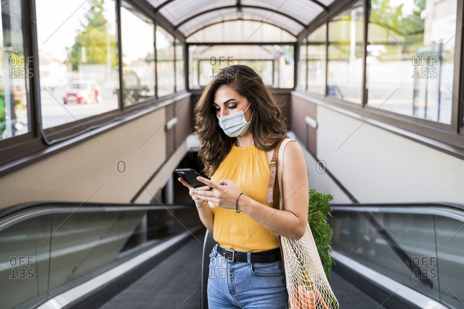 Young woman text messaging while standing with mesh bag on moving walkway at subway