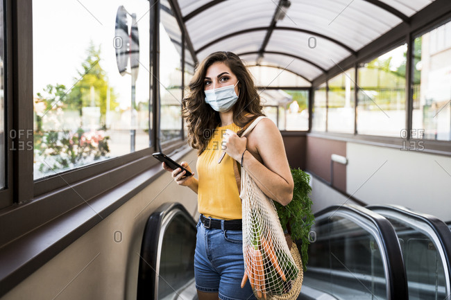 Young woman standing with vegetables in mesh bag against moving walkway at subway