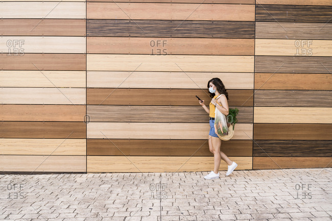 Young woman using smart phone while walking with mesh bag by wooden wall