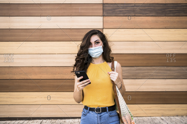 Young woman holding smart phone and mesh bag while standing against wooden wall