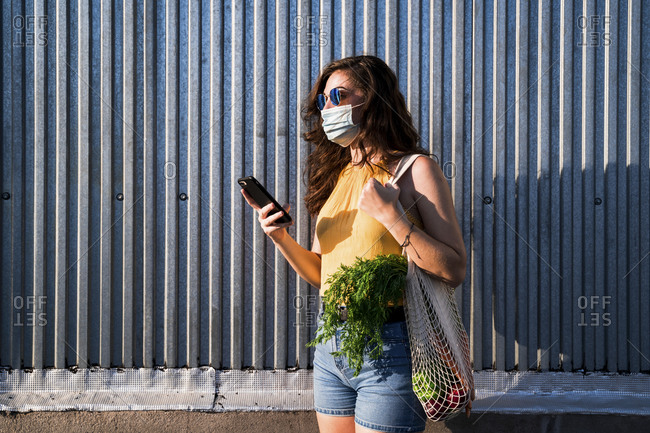 Young woman with vegetables in reusable mesh bag using smart phone while standing against metallic wall