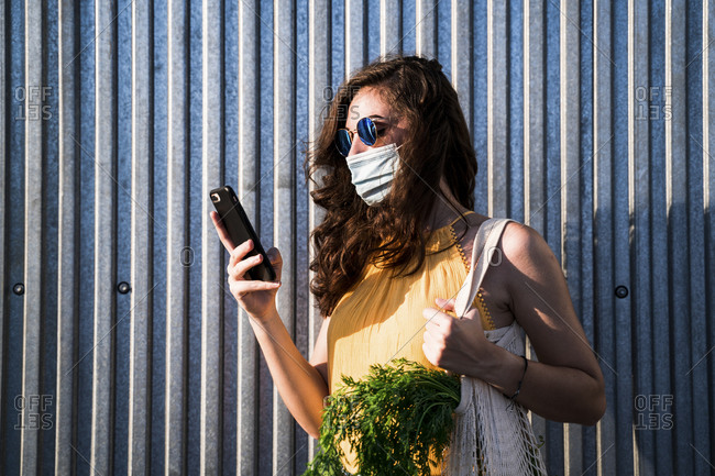 Young woman wearing face mask while standing with mobile phone and reusable mesh bag against metallic wall