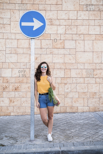 Smiling young woman leaning on directional sign against wall in city