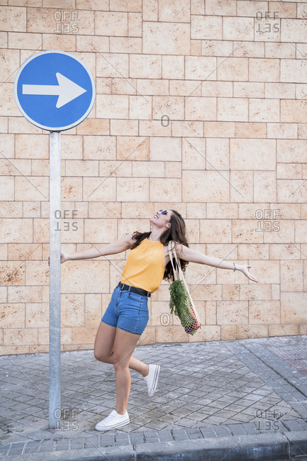 Playful young woman holding directional sign while standing on sidewalk against wall in city