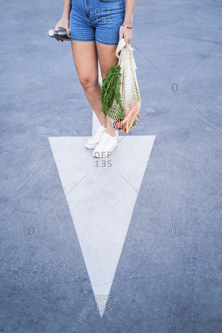 Young woman carrying reusable mesh bag and bottle while standing on arrow symbol road marking in city