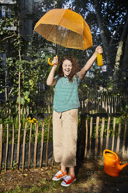 Cheerful woman with mouth open holding bottle and umbrella while standing at back yard enjoying sunny day