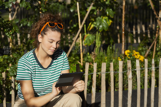 Young woman using tablet in garden