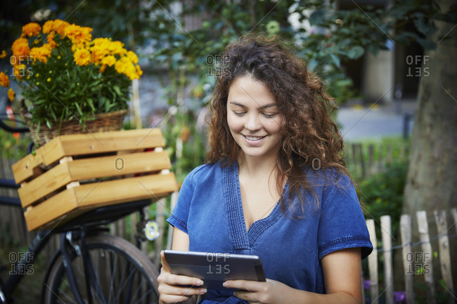 Smiling young woman using tablet in garden