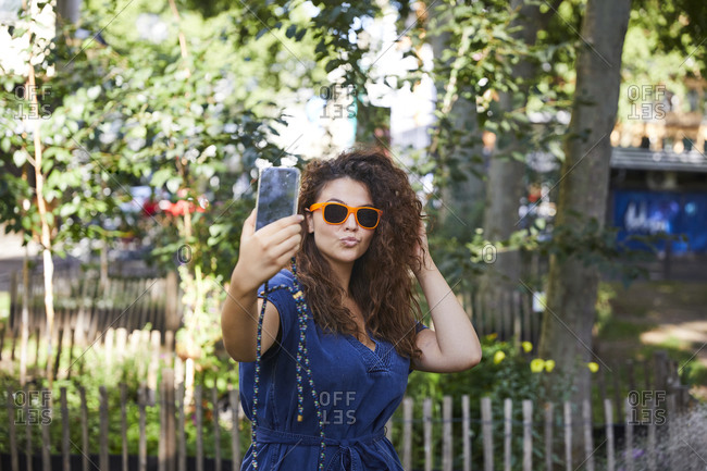 Young woman with sunglasses taking a selfie with her smartphone in garden